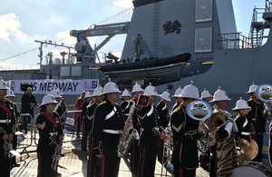 The Royal Marines band plays with HMS Medway in the background.