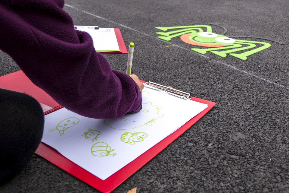 A child drawing one of the new playground decorations on a clipboard