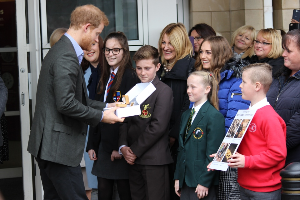 Prince Harry is presented with a Passchendaele 100 brass poppy badge by Phoebe Taylor, Crown Copyright, All Rights Reserved