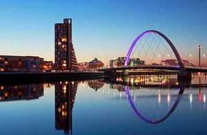 Glasgow city scene with reflection of the Clyde Arc Bridge at dusk.