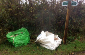 Two very large builders' waste bags left by roadside next to fingerpost