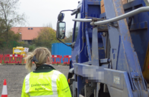 An Environment Agency Officer by the side of a waste carrier lorry.