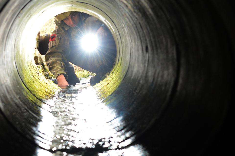Lance Corporal Joe Lightowler searches a culvert