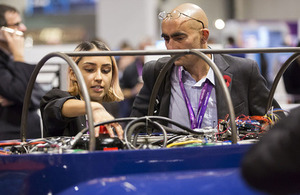 HYPED's Elisha Jhoti with a delegate, discussing the prototype Hyperloop