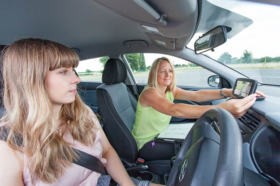 Driving test candidate with a driving examiner setting up a sat nav