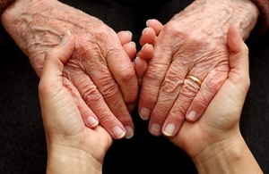 Carer and elderly person holding hands