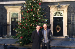 Welsh Secretary Alun Cairns joins victorious grower Robert Morgan of Gower Fresh Christmas Trees, who's tree adorns the outside of No10