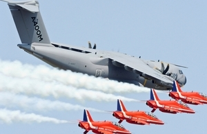 An A400M Air Transporter is accompanied by the Red Arrows