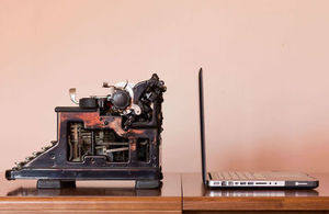 An old typewriter next to a new laptop