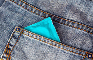 A condom packet poking out of a jean pocket