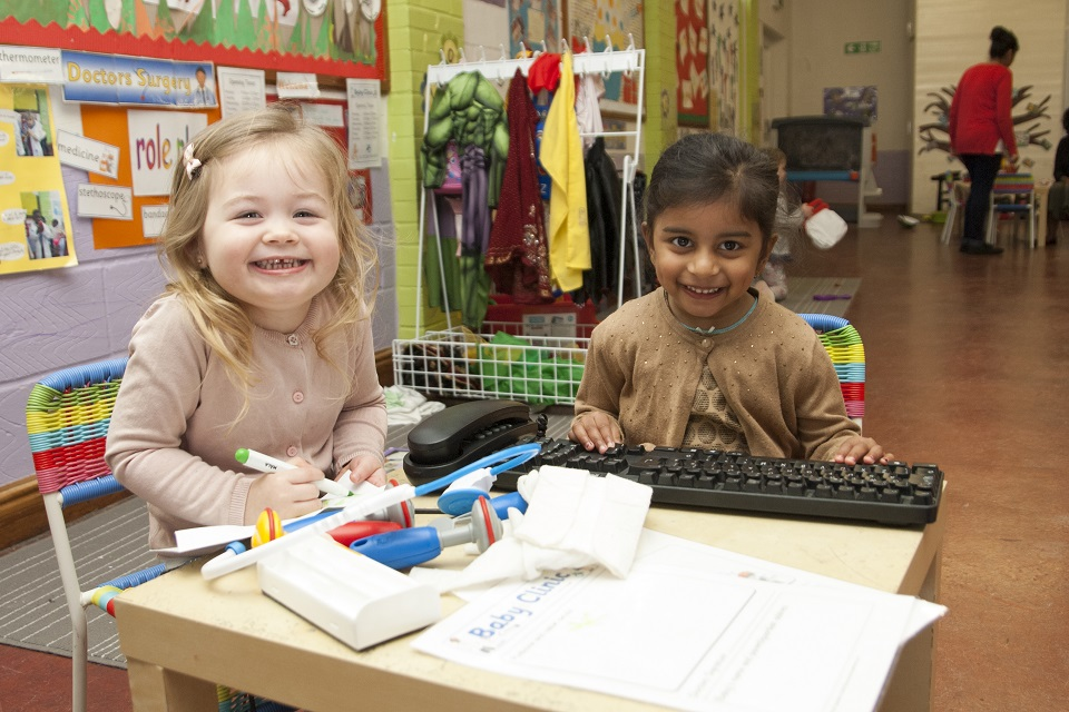 Two girls sitting at a table in a nursery.
