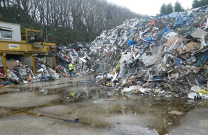 A tall pile of waste stored at the waste transfer station