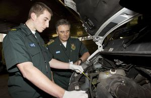 Apprentice NHS mechanic examines an ambulance engine
