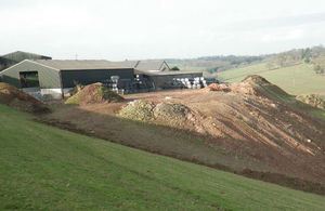 Huge mounds of rubble in front of hilltop farm surrounded by green pastures
