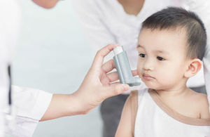 Paediatrician shows young boy how to use an asthma inhaler