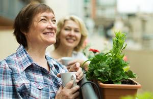Older woman drinking tea on her balcony
