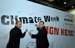 Secretary of State Edwards Davey signing the Climate Week 'pledge wall' at Ecobuild
