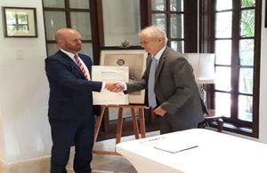 Ambassador Damion Potter hands over the Order to Dr. Cooke