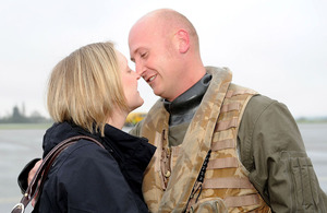 A member of 217 Flight leans in for a kiss from his wife upon his return from deployment in the Indian Ocean [Picture: Leading Airman (Photographer) Caroline Davies, Crown copyright]