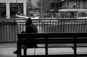 Black and white photo of a man on a bench by a canal