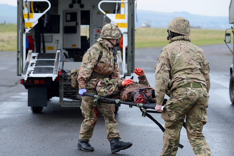 Commandos transporting a simulated casualty to a waiting ambulance