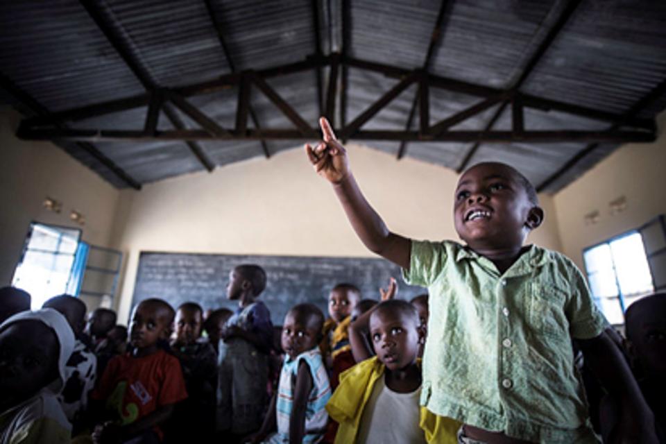 A boy raises his hand in class, Burundi. UNICEF Burundi/Colfs