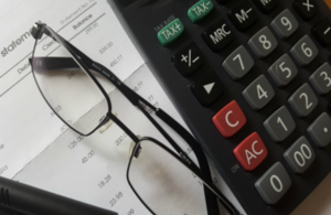 calculator, glasses and bank statement