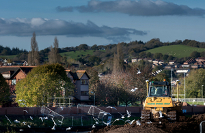 A digger on a flood embankment as part of the new Exeter flood defence, with new flood wall in the background