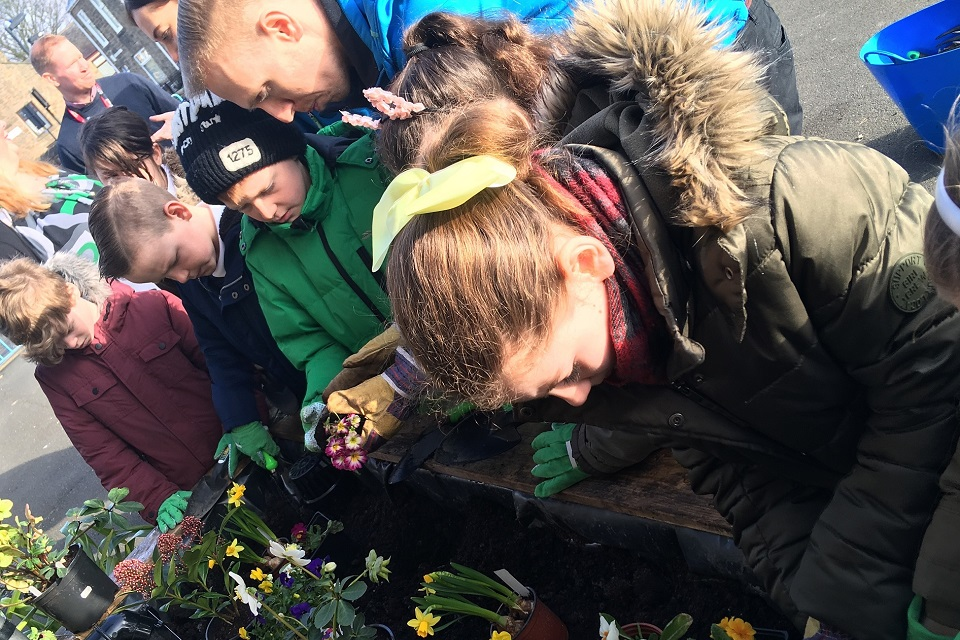 Image shows youngsters at the school putting flowers in the new rain planter
