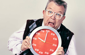 Image of a man holding a clock looking anxious.