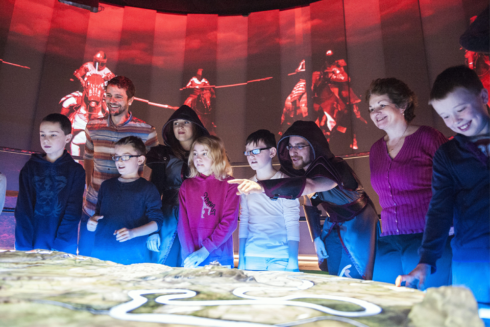 Battle Master leads a group of school pupils through a simulated battle in the Battle Room, Battle of Bannockburn Centre