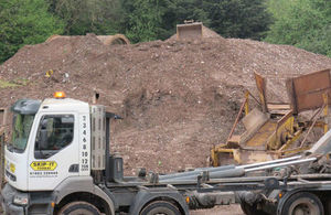 Picture of a branded skip carrier parked in front of a large pile of brown waste