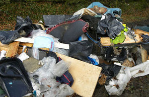 Photo of rubbish, wood panels and plastic strewn across ground