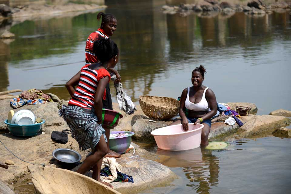 Women washing clothes by a river in Sierra Leone