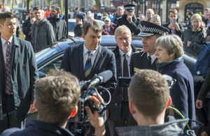 Prime Minister Theresa May visiting Salisbury, pictured with police officers and a crowd of people.