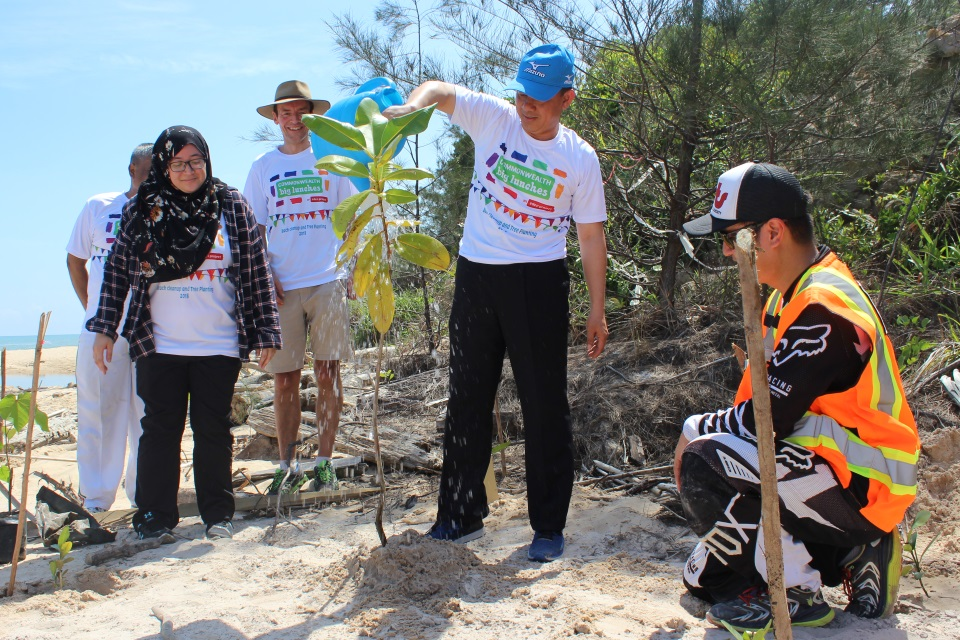 The Minister of Culture, Youth and Sports watering a sapling he had planted on Berakas Beach