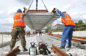 Workers laying rail track.