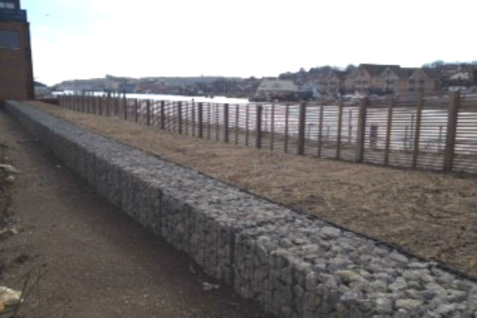 Rock-filled wire mesh boxes used to construct flood defences at edge of sea bay