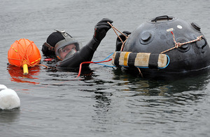 Able Seaman Diver Philip Rowland attaches explosives to a floating mine during a demonstration at the new facility [Picture: Richard Watt, Crown copyright]