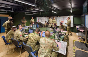 A room that shows many service personnel at work in Joint Battlespace Management.