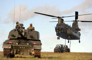 Shows a merlin helicopter and tank in shot together.