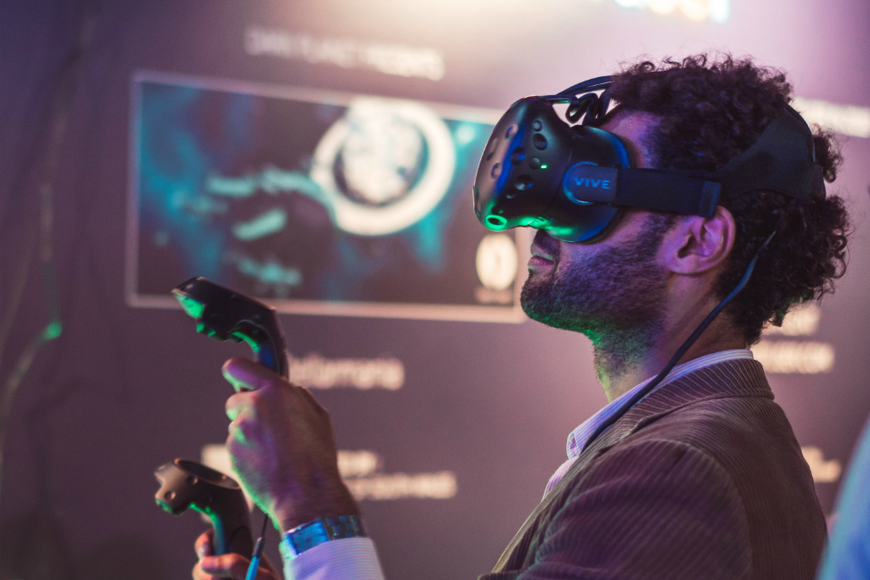 A man in a virtual reality headset holding 2 wireless controllers. (Courtesy of the UK Games Fund).