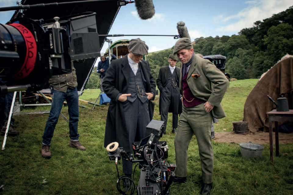Actors and camera crew from 'Peaky Blinders' filming in a field.