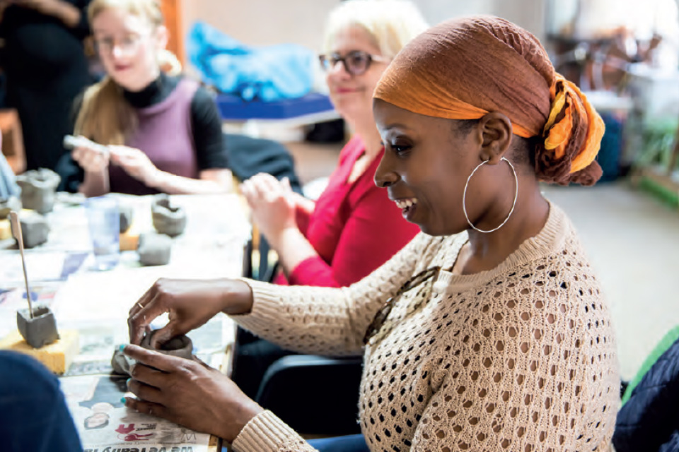 A group of women making clay sculptures at a Hey Clay event.