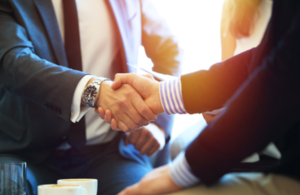 A photograph of two businessmen shaking hands
