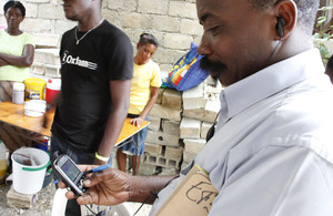 An aid worker uses a mobile phone in Haiti after the 2010 earthquake. Picture: Russell Watkins/DFID