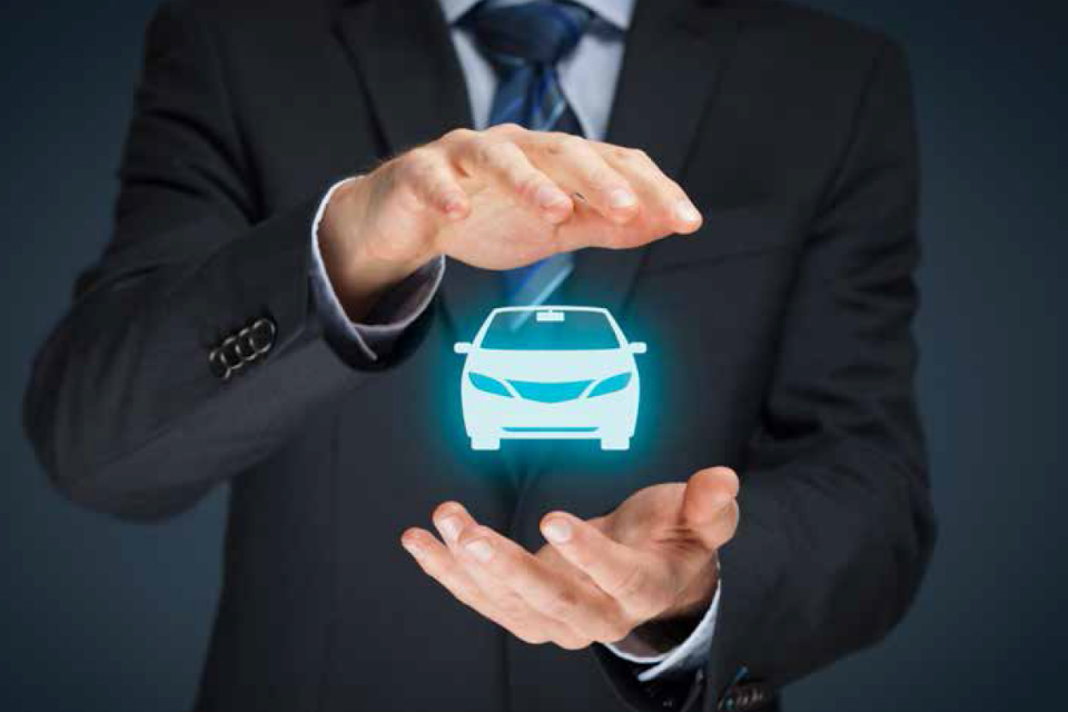Hands holding a graphic of a car (credit: Jirsak/iStock - ID612225244).