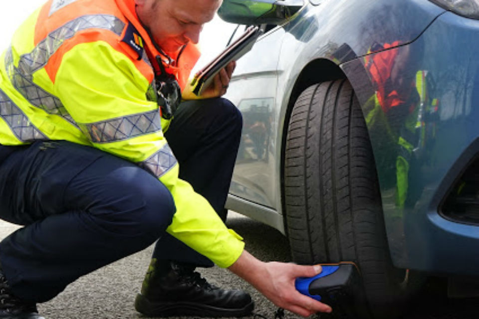 Traffic officer checking a tyre