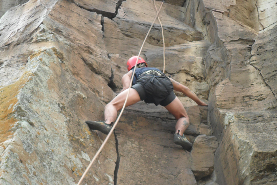 A soldier scaling a rock face