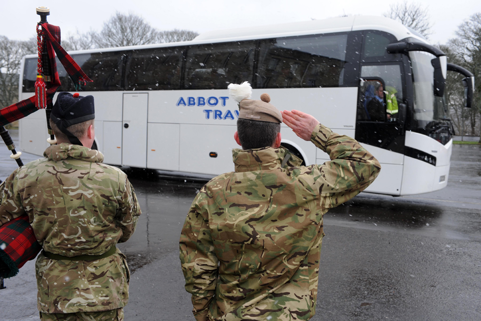 A bagpiper and senior officer salute the departing troops at Glencorse Barracks